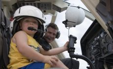 toddler sitting in passenger seat of helicopter with Dad in pilot's seat