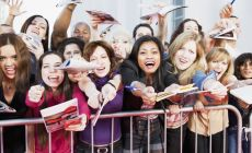 crowd of fans behind a fence screaming and waving autograph books
