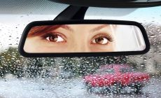 womans eyes seen in car rear view mirror